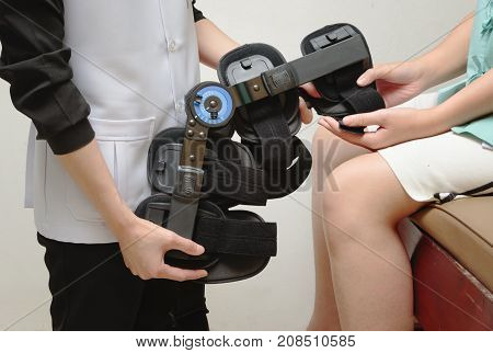 Physical therapist fitting a knee brace to patient knee in rehab center