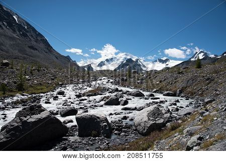 Wildlife Altai river running from the mountains and blue sky with clouds