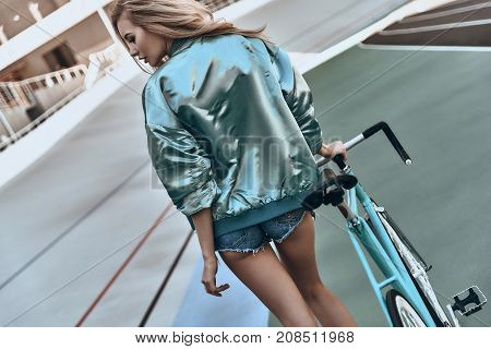 Just enjoying the day. Rear view of attractive young woman in casual clothing walking with her bicycle while spending time outdoors