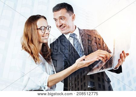 Working process. Delighted young man with a laptop in his hands looking attentively at his colleague and smiling