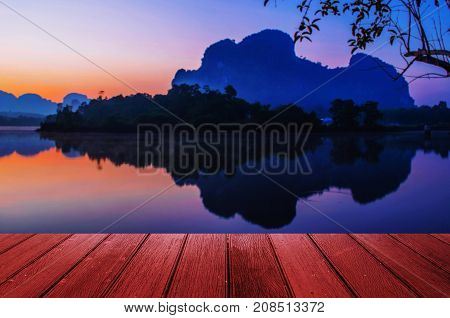 empty wooden table floor or terrace copy space for display of product or object presentation with beautiful landscape colorful mountain silhouette reflection in lake in summer background
