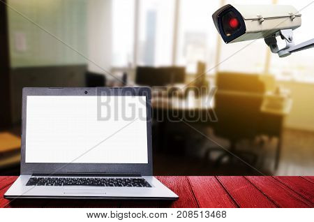 white blank screen laptop computer on wooden desk with CCTV security indoor camera system operating in office technology internet surveillance security and safety technology concept