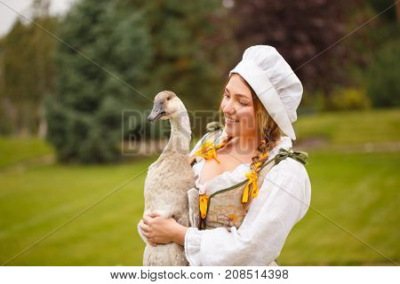 a peasant woman with a goose in her arms amid a meadow. fairy tale
