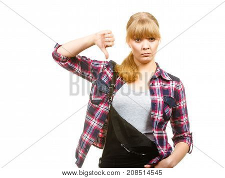 Gardening concept. Attractive woman in dungarees and pink check shirt showing thumb down. Isolated background