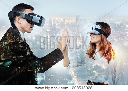 Digital touch. Impressed surprised elegant man touching the right hand of his girlfriend while they both wearing modern virtual reality glasses