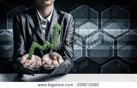 Businessman in suit presenting green plant in form of growing graph in hands with media icons on background.