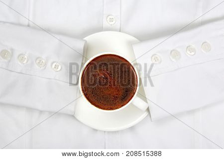 Cup of black coffee on a white shirt with sleeves