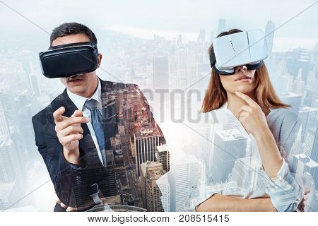 Observing beauty. Two curious young colleagues standing near each other and observing interesting views in virtual reality glasses