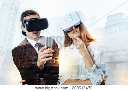 Curious reality. Elegant man in a black suit wearing amazing virtual reality glasses together with his young thoughtful colleague