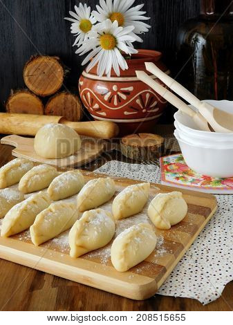 Raw vareniki (Ukrainian cuisine meal) prepared for cooking are lying on a chopping board sprinkled with flour