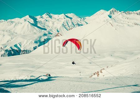 Paraglider tandem flying over Gudauri . Colorful parachute. Active lifestyle Extreme hobbies. Paragliding explore Georgia. Adventure travel. Winter mountain landscape. Fearlessness concept. Freedom.