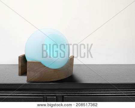 Colored Air Freshener In Glass Container On Black Desk