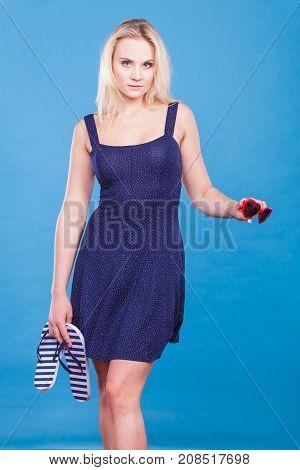 Woman Wearing Short Dress Holding Flip Flops And Sunglasses