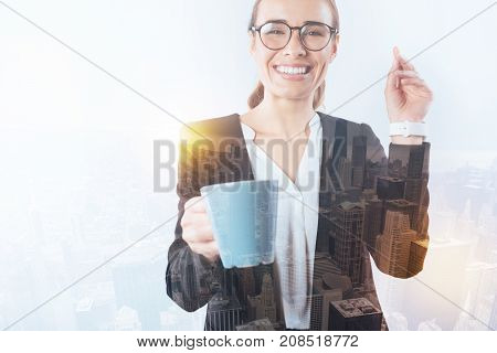 Funny joke. Nice young happy woman laughing at the joke while showing her new beautiful blue cup