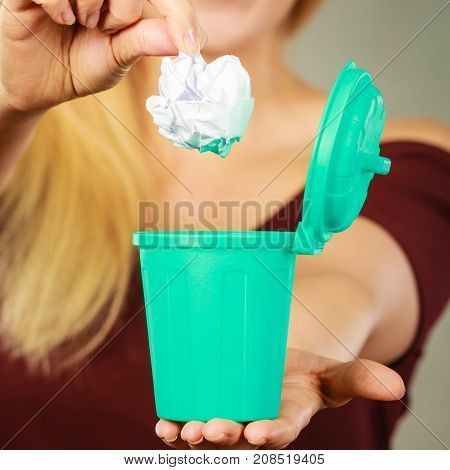 Cleaning Woman putting paper into tiny trash can basket showing how to deal with rubbish