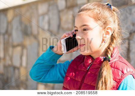 Beautiful girl talking on a smartphone in a red vest on the outdoor.Handsome smiling girl with mobile phone walking on outdoor. Young girl receiving good news by phone. Portrait smiles girl