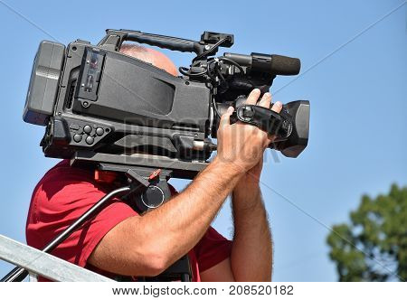 Cameraman works outdoor in summer time against sky