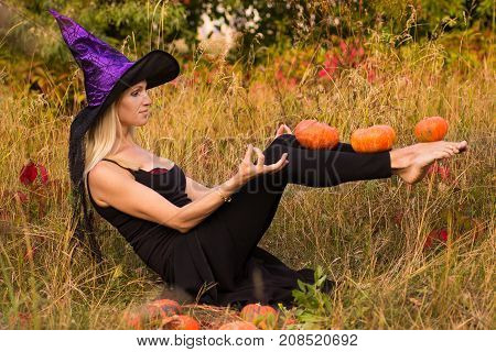 Young Glad Girl In Witch Costume Practicing Yoga