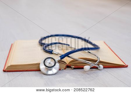 Beautiful stethoscope lying on a reference books. Stethoscope with open book on wooden background. Medical literature concept. copy space for text, selective focus