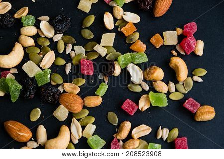 Composition with dried fruits and assorted nuts. Delicacies. Various nuts on stone table. Different kinds of nuts. Close up on a black background. Top view, flat lay. copy space for text