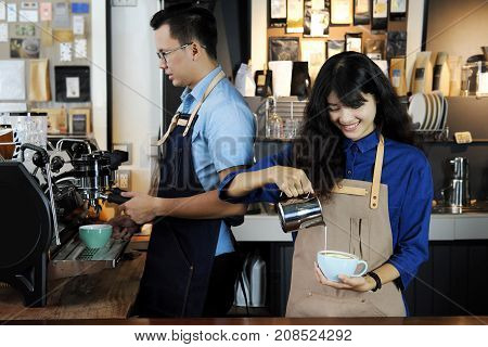 Two of asian barista making latte or cappucino coffee in coffee shop. Cafe restaurant service Small business owner food and drink industry concept.