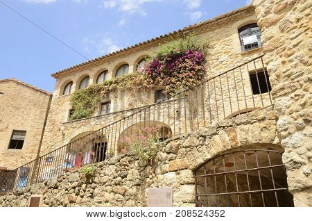 PALS, SPAIN - JULY 25, 2017: Beautiful stone house with flowers on its wall in the medieval village of Pals located in the middle of the Emporda region of Girona Catalonia Spain.