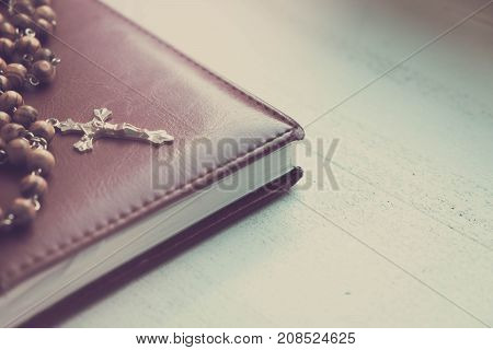 The silver crucifix and a pen on the a blank note book over wooden background, christian concept