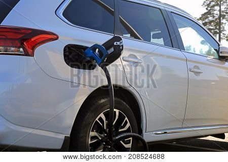 TOIJALA FINLAND - SEPTEMBER 24 2017: Detail of white Mitsubishi electric SUV connected to car battery charging port.