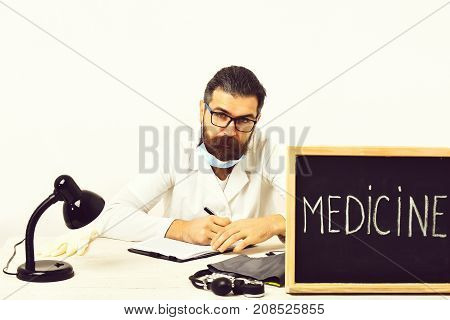 Bearded Caucasian Doctor Sitting At Table With Board