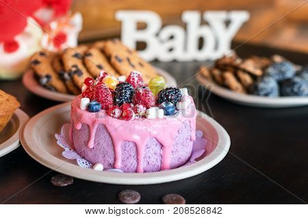 Birthday cakes and muffins with wooden greeting signs on rustic background. Wooden sing Baby and holiday sweets