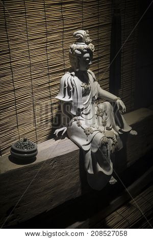 chinese traditional white stone statue sculpture on display under dramatic moody light in xiamen china