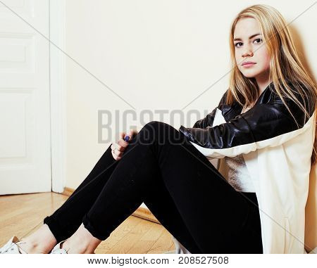 young pretty teenage blond girl sitting on floor at home despair sad alone, lifestyle people concept
