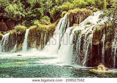 Krka waterfalls. Croatian national park. Beautiful natural scene. Flowing water and greenery. Croatia Europe. Side view. Retro photo filter.