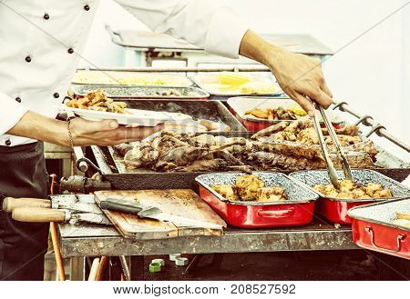 Masterchef serves grilled meat. Detail food and hands scene. Feast theme. Yellow photo filter.