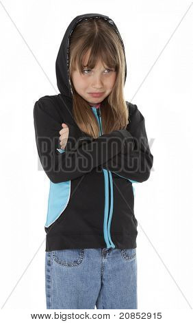 Sad young girl, arms crossed, standing on white background.