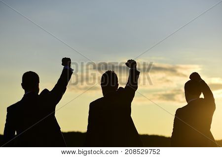 Silhouettes Of Men Putting Their Fists Up. Victory And Success