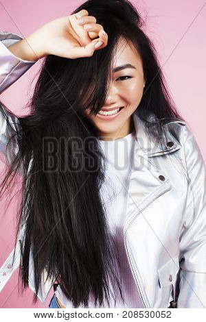 young pretty stylish hipster asian girl posing emotional isolated on pink background happy smiling cool smile, lifestyle people concept closeup