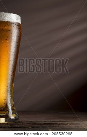 Close up of a wet glass of cold light beer with foam. Selective focus
