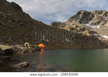 Night landscape of a high mountain lake in an archipelago in the northern Caucasus with a luminous tourist tent on the lake shore. High-altitude lake in the moonlight High-altitude lake in arkhyz. North Caucasus
