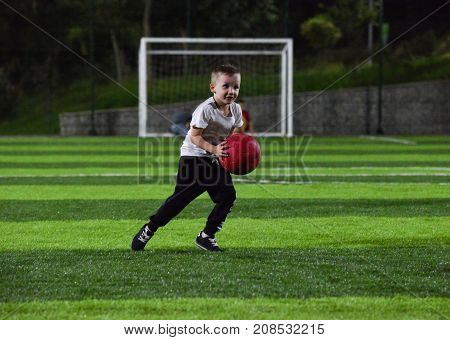 happy and active child throws the red ball on the background of a football gate in the twilight time