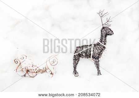 Hand made Christmas deer and Christmas sleigh against a white cotton wool background. Handmade Christmas decoration made of wire.