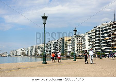 Thessaloniki Greece - April 14 2017 : People walking on the seafront promenade in the afternoon