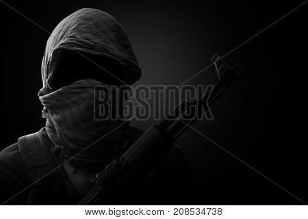 Blurry Background of Terrorist carry weapon hidden in darkness. terrorism concept. on black background with dim light. Black and White.