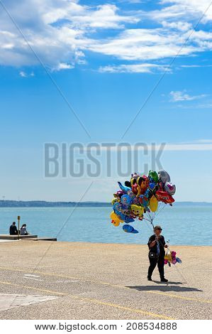 Thessaloniki Greece - April 14 2017 : Woman with colorful balloons for sale walking along Thessaloniki seafront
