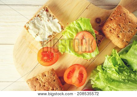 Cooking vegetarian burger with tomatoes cheese and lettuce