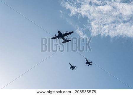 Madrid Spain - October 12 2017: Hercules KC-130 tanker aircraft refuelling in flight two jet fighters in Spanish National Day Parade.