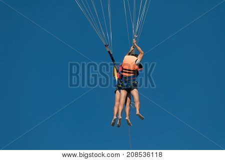Two people on parachute flying over the beach blue sky and sunny day. Flying high on the parachute fine entertainment and extreme