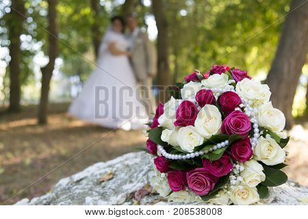 Bride's bouquet is sharp and the bride and groom are out of focus