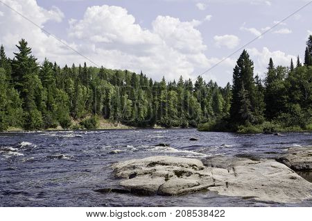 Wide view of a some small river rapids off a rocky shoreline surrounded by trees and greenery at Pabineau Falls near Bathurst, New Brunswick on a bright sunny day with blue skies and clouds in August.