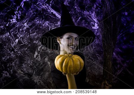 Halloween  Witch holding a pumpkin and a broom. smiling woman dressed like a fairy witch
